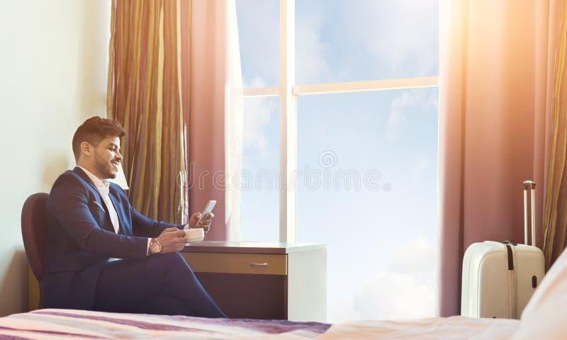 Viaggio di affari Caffè bevente di Using Phone And dell'uomo d'affari fotografia stock libera da diritti