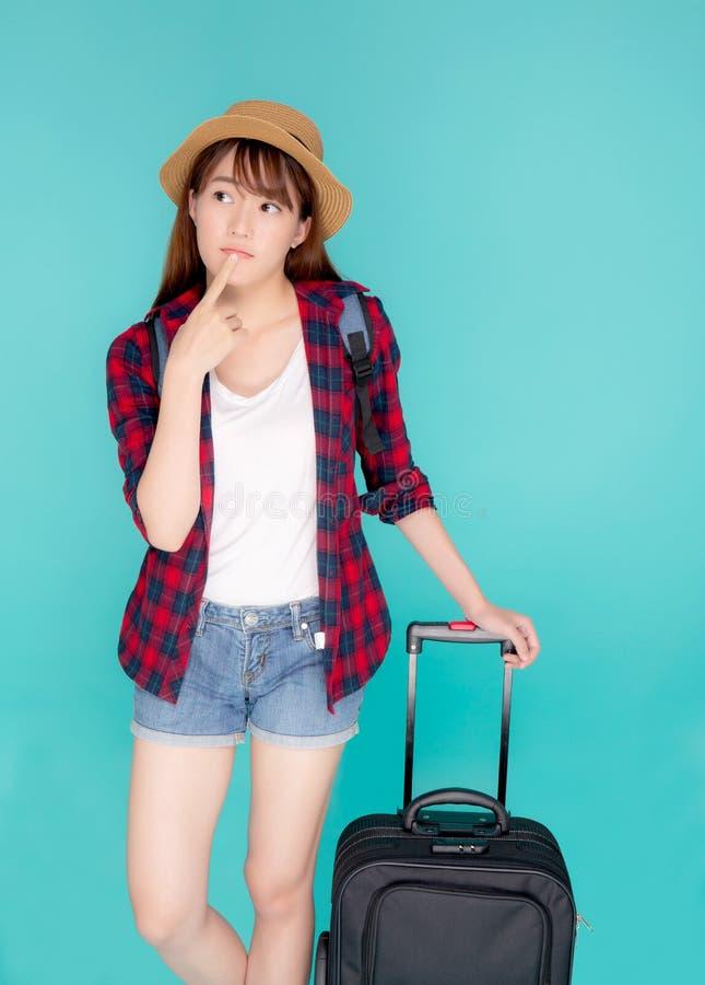 Viaggio di pensiero di idea della bella donna asiatica del ritratto giovane nella vacanza con bagagli isolati su fondo blu immagine stock