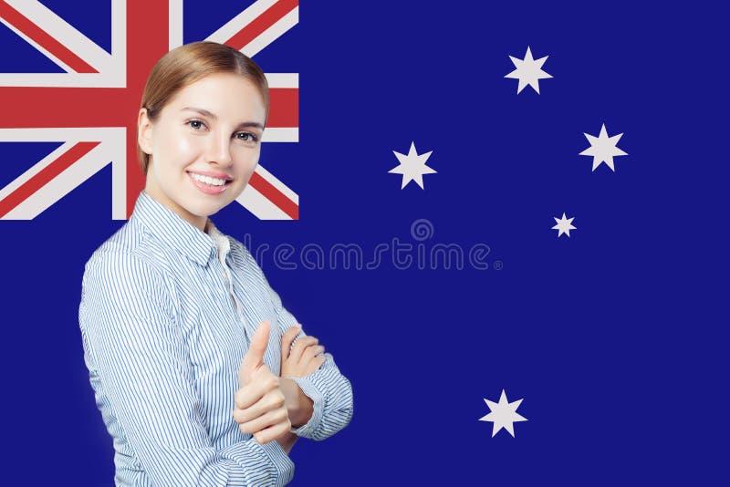 Viaggio e studio nel concetto dell'Australia con la studentessa sorridente sveglia contro il fondo australiano della bandiera immagine stock libera da diritti