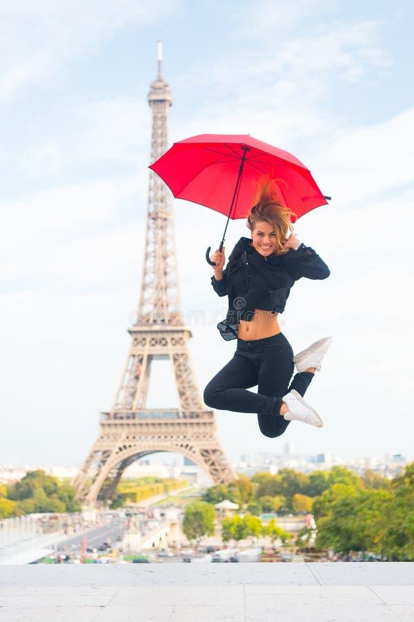 Viaggio felice della ragazza a Parigi, Francia La donna salta con l'ombrello di modo Parigino su fondo bianco Donna con fotografie stock