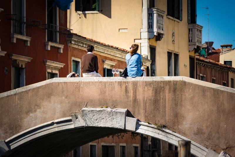 Viaggio in Italia La gente che gode di un bicchiere di vino su un ponte sopra il canale a Venezia, Italia fotografia stock