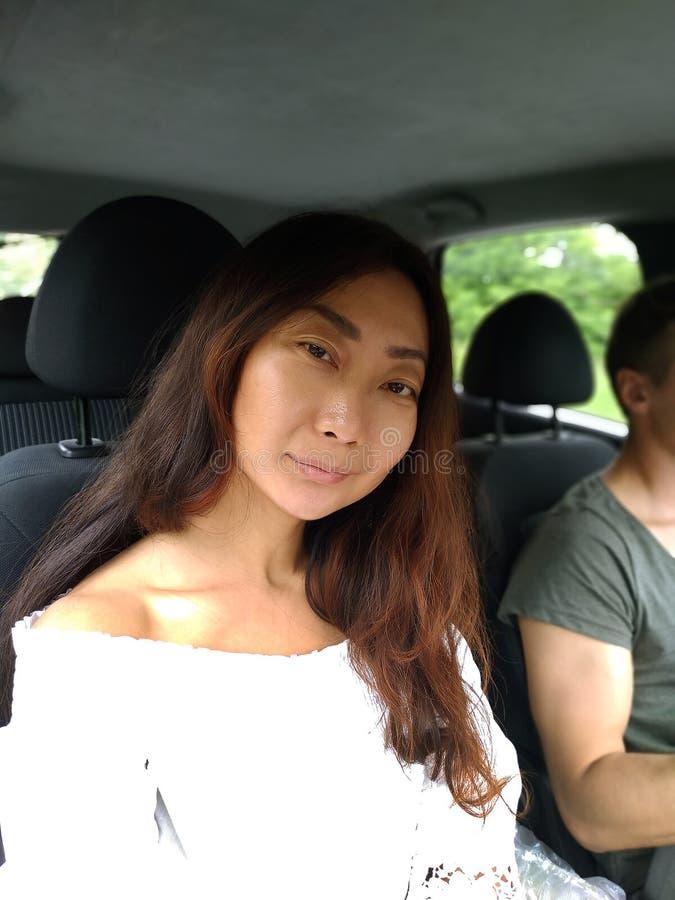 Viaggio stradale, viaggio, vacanze estive e concetto della gente - coppia felice che guida in automobile, ragazza che esamina mac immagine stock libera da diritti