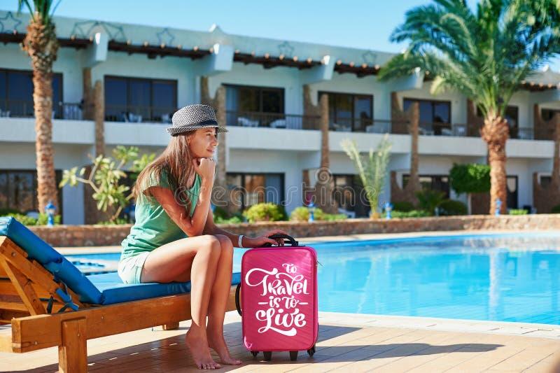 Viaggio, vacanze estive e concetto di vacanza - bella donna che cammina vicino all'area di stagno dell'hotel con la valigia rossa immagine stock