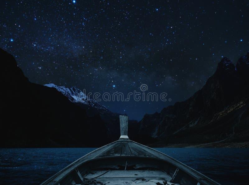 Viajando en el lago en la noche por el barco, el cielo por completo de la estrella y la vía láctea con el valle de las montañas imágenes de archivo libres de regalías