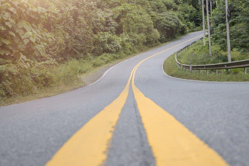 Viajando en la carretera de asfalto, hay una trayectoria curvada al bosque, con los árboles abundantes foto de archivo libre de regalías