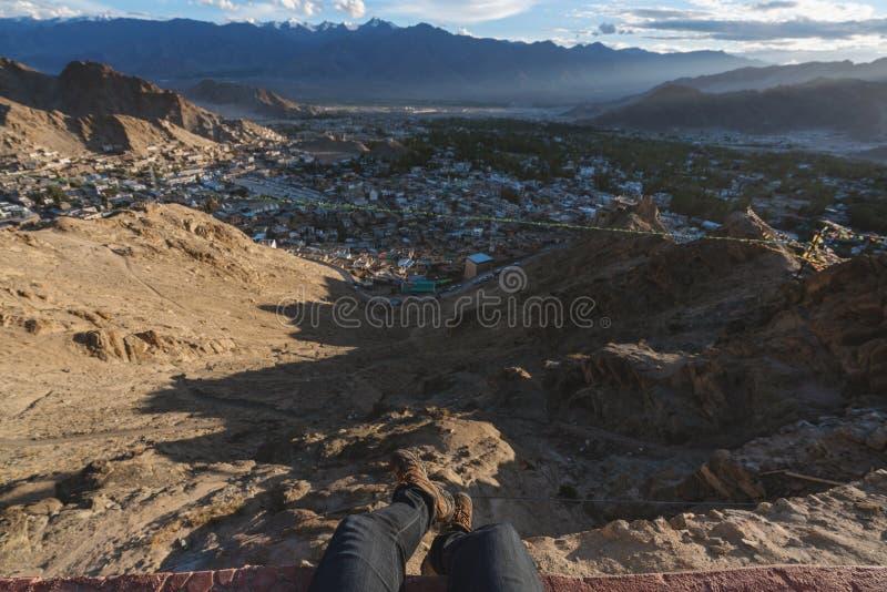 Viajando en la ciudad de Leh, en Ladakh, la India un hombre que se sienta en el acantilado que disfruta de la opinión de la ciuda foto de archivo