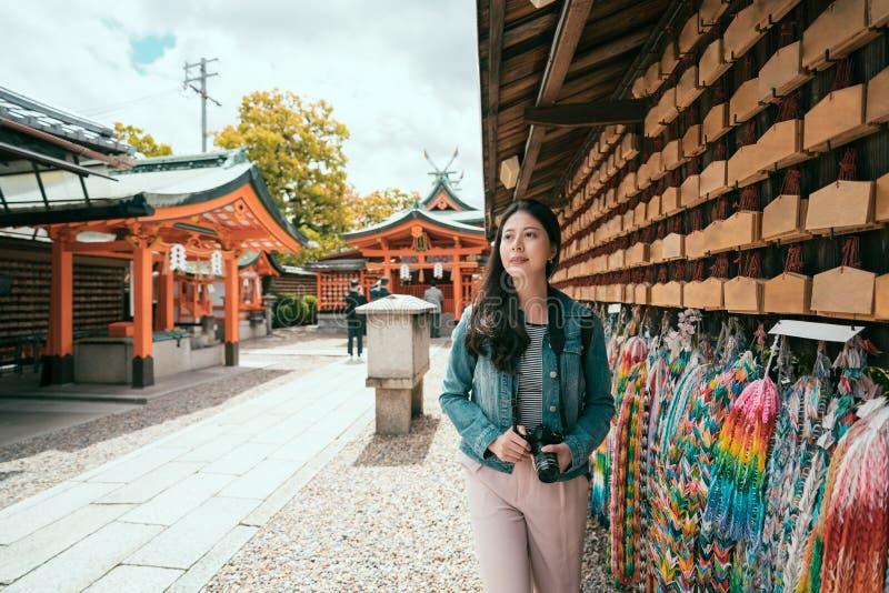 Viajante asiático da menina que anda ao longo da parede rezando fotos de stock