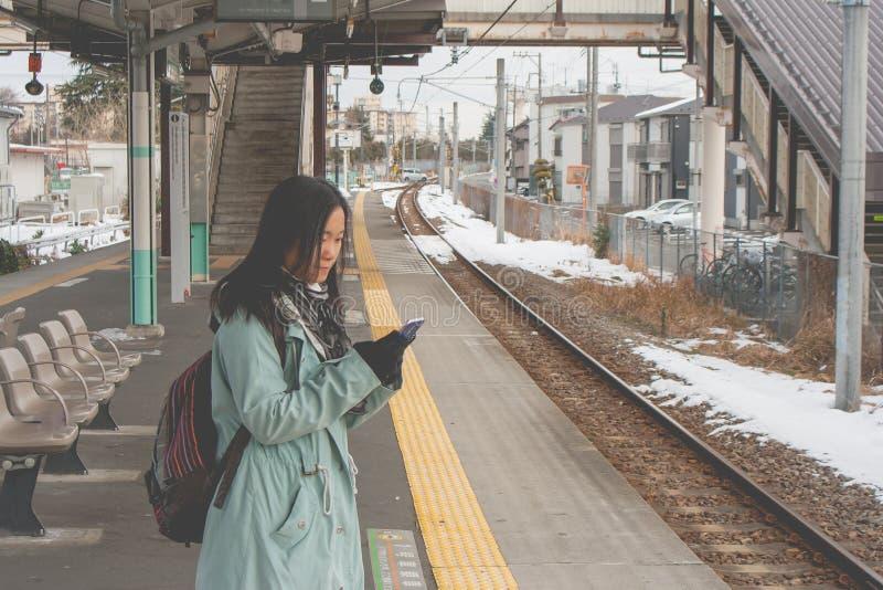 Viajante asiático da mulher do retrato que está na estação de trem e que joga seu smartphone fotografia de stock royalty free