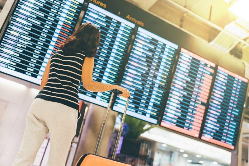 Viajante asiático da mulher que olha a tela da informação do voo em um aeroporto, guardando o conceito da mala de viagem, do curs fotografia de stock royalty free