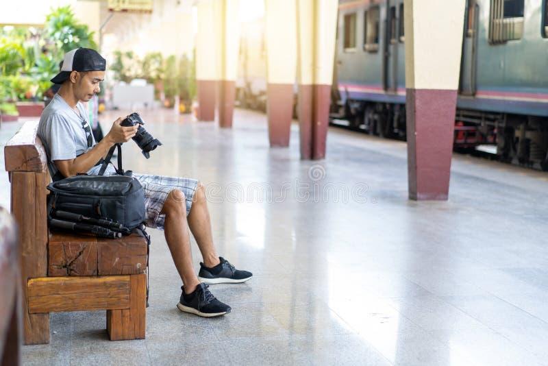 Viajante asiático do homem com a câmera da foto da terra arrendada e trouxa no estação de caminhos de ferro fotos de stock