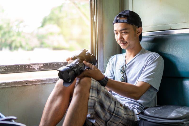 Viajante asiático do homem com a câmera e a trouxa da foto da terra arrendada da mão fotos de stock