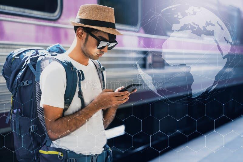 Viajante asiático novo com a trouxa na estrada de ferro, a trouxa e o chapéu no estação de caminhos de ferro com um viajante, con fotografia de stock
