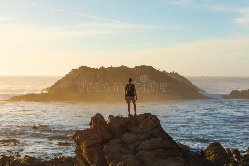 Viajante com mochila desfrutando da vista oceânica, homem caminhando no pôr do sol, conceito de viagem, Califórnia, EUA fotos de stock