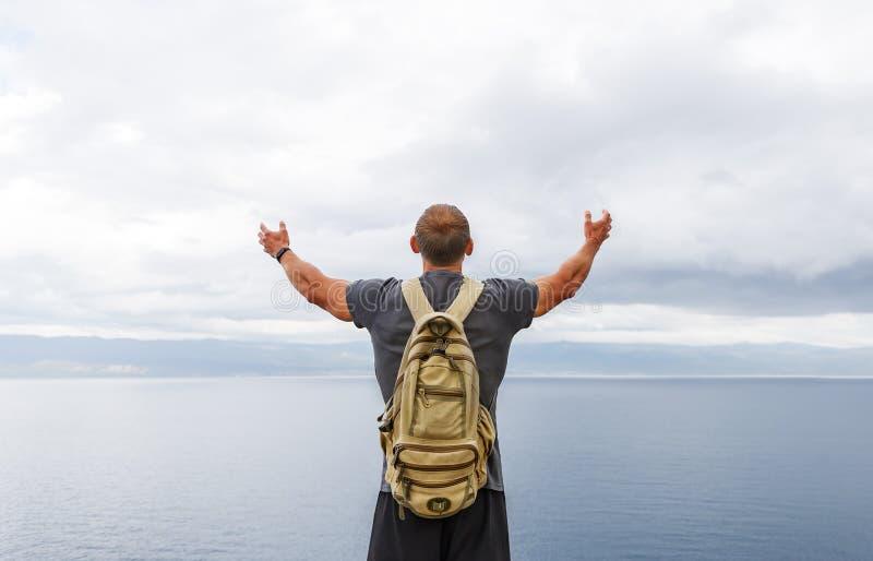 Viajante com suporte da trouxa na costa e vista do mar com mãos levantadas no ar imagens de stock royalty free