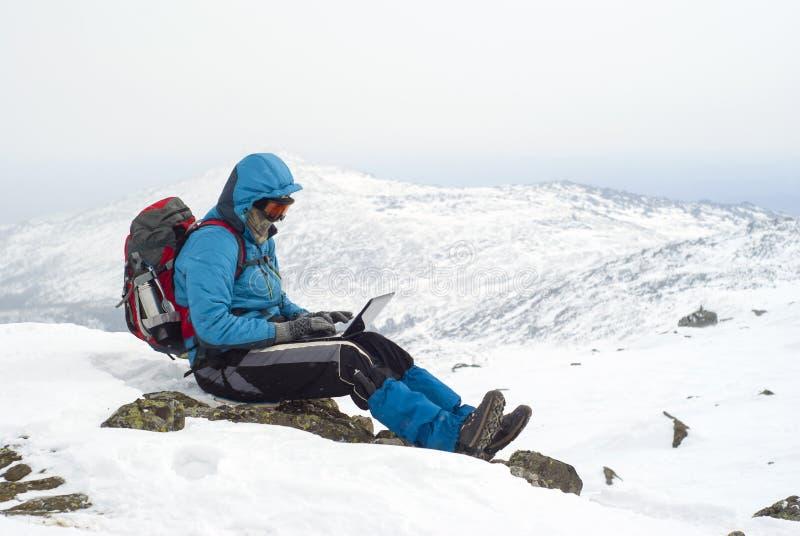 Viajante com um portátil no inverno sobre uma montanha foto de stock royalty free