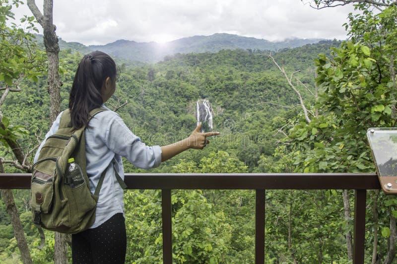 Viajante da jovem mulher com o relaxamento da trouxa exterior com waterfa fotos de stock