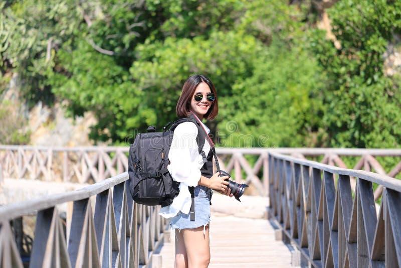 Viajante da jovem mulher com trouxa que aprecia e que guarda a came de DSLR fotos de stock