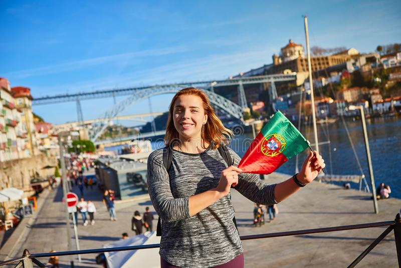 Viajante da jovem mulher que está para trás com a bandeira portuguesa, apreciando a opinião bonita da arquitetura da cidade no ri imagens de stock royalty free