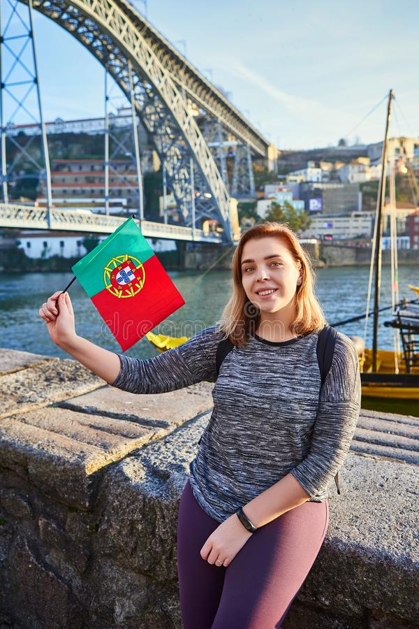Viajante da jovem mulher que está para trás com a bandeira portuguesa, apreciando a opinião bonita da arquitetura da cidade no ri fotografia de stock