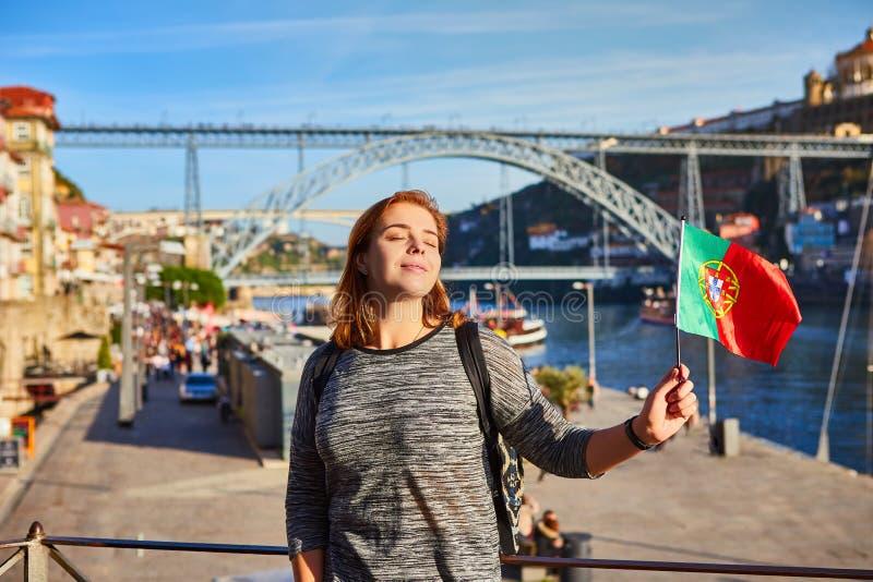 Viajante da jovem mulher que está para trás com a bandeira portuguesa, apreciando a opinião bonita da arquitetura da cidade no ri imagem de stock
