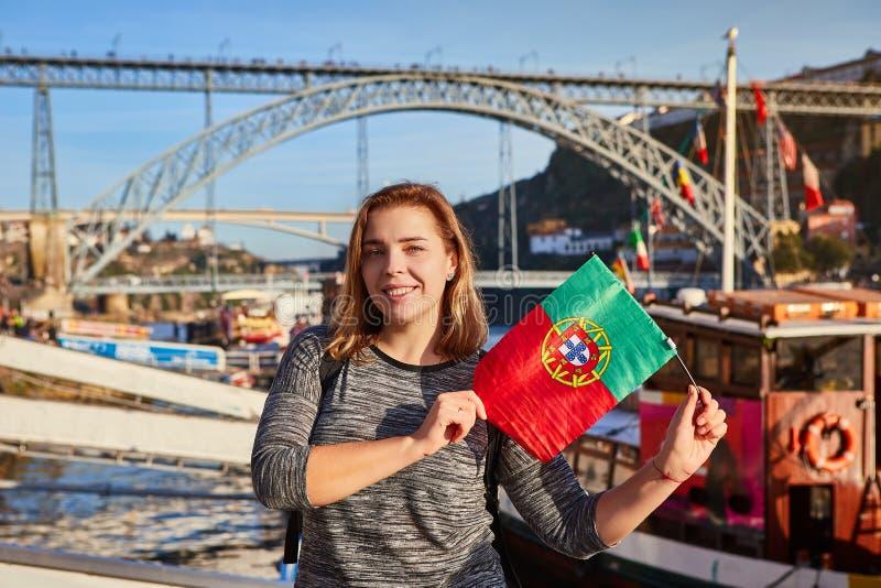 Viajante da jovem mulher que está para trás com a bandeira portuguesa, apreciando a opinião bonita da arquitetura da cidade no ri foto de stock