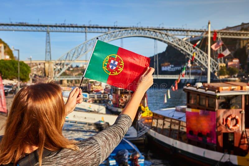 Viajante da jovem mulher que está para trás com a bandeira portuguesa, apreciando a opinião bonita da arquitetura da cidade no ri imagem de stock royalty free