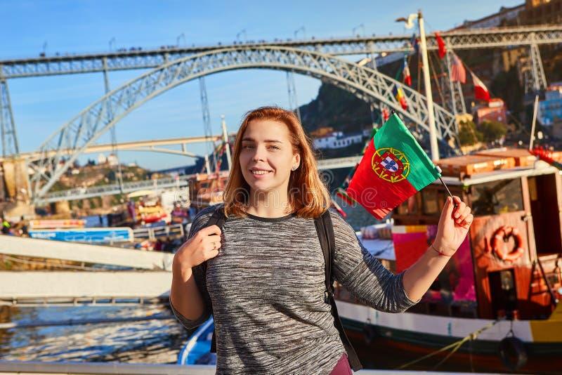 Viajante da jovem mulher que está para trás com a bandeira portuguesa, apreciando a opinião bonita da arquitetura da cidade no ri imagens de stock