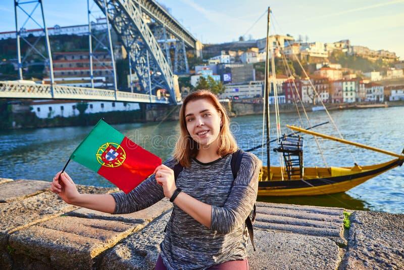 Viajante da jovem mulher que está para trás com a bandeira portuguesa, apreciando a opinião bonita da arquitetura da cidade no ri fotografia de stock royalty free