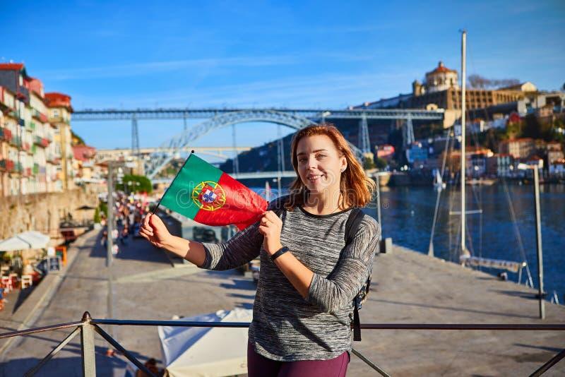 Viajante da jovem mulher que está para trás com a bandeira portuguesa, apreciando a opinião bonita da arquitetura da cidade no ri fotos de stock