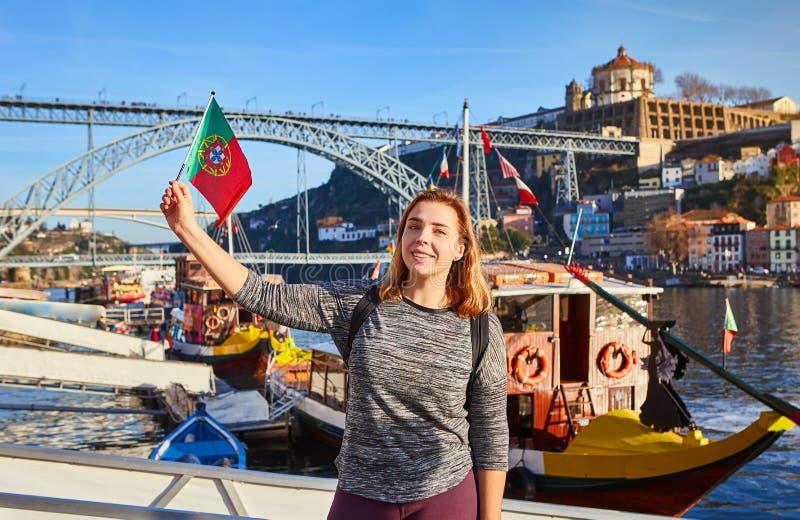 Viajante da jovem mulher que está para trás com a bandeira portuguesa, apreciando a opinião bonita da arquitetura da cidade no ri fotos de stock royalty free