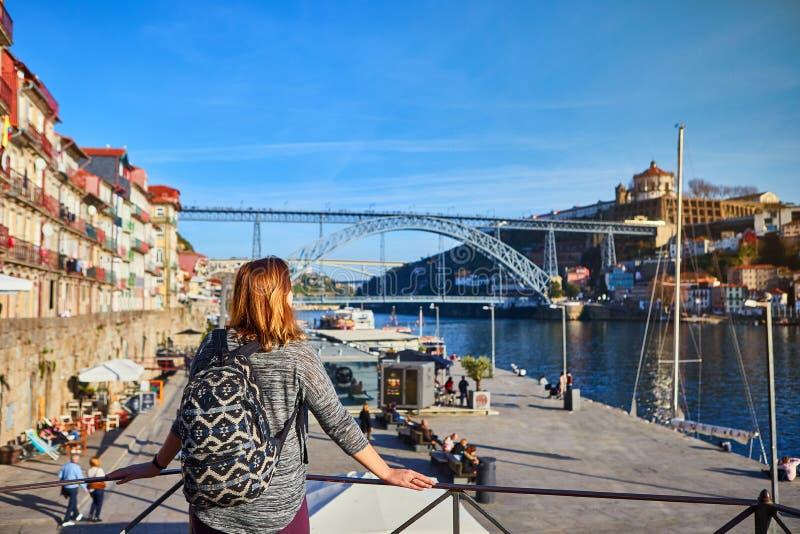 Viajante da jovem mulher que está para trás de apreciação a opinião bonita da arquitetura da cidade no rio, na ponte e nos barcos fotos de stock royalty free