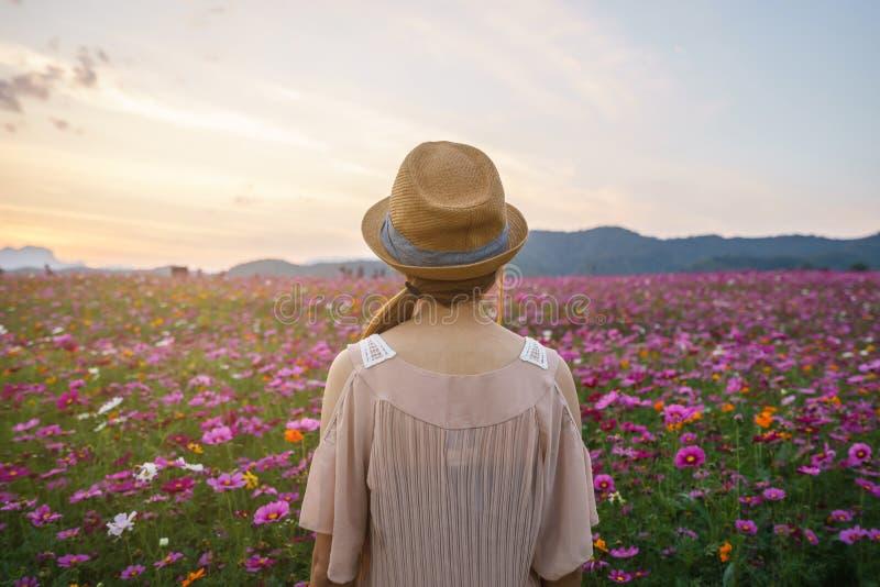 Viajante da jovem mulher que olha o campo de flores bonito imagem de stock
