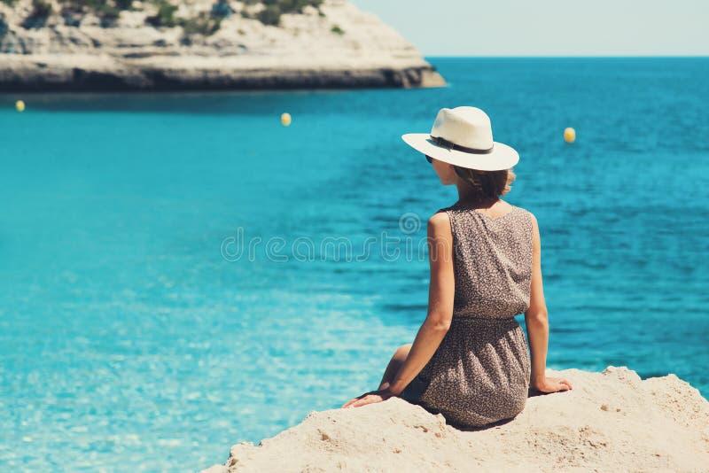 Viajante da jovem mulher que olha o mar, o curso e o conceito ativo do estilo de vida Conceito do abrandamento e das férias imagem de stock royalty free