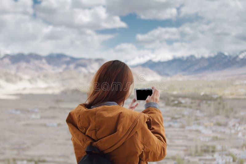 Viajante da jovem mulher que toma a foto pelo smartphone que explora montanhas bonitas imagens de stock royalty free