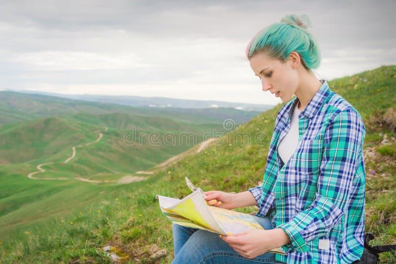 Viajante da menina com o cabelo multi-colorido que senta-se no cartão e na terra arrendada da leitura da natureza um compasso à d imagem de stock royalty free