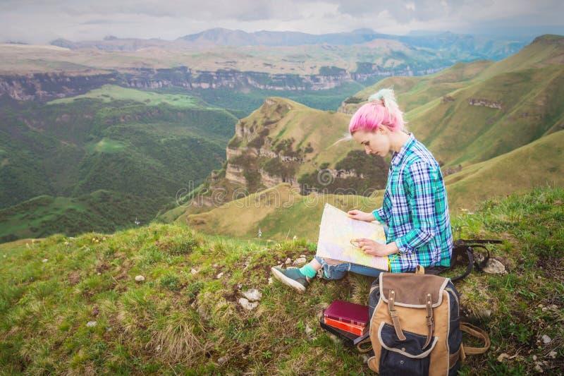 Viajante da menina com o cabelo multi-colorido que senta-se no cartão e na terra arrendada da leitura da natureza um compasso à d fotos de stock royalty free