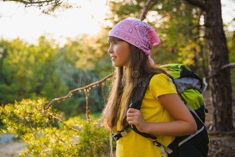 Viajante da menina com a trouxa na aventura da floresta do monte, curso, conceito do turismo fotografia de stock royalty free