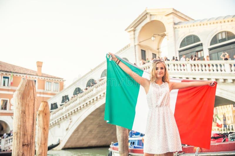 Viajante da menina do jovem adolescente com a bandeira italiana antes da ponte histórica Ponte De Rialto no centro de Veneza - It foto de stock