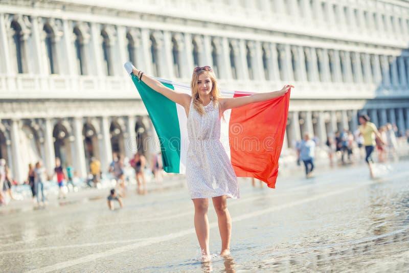 Viajante da menina do jovem adolescente com a bandeira italiana no St Mark & no x27; quadrado de s em Veneza - Italia foto de stock royalty free