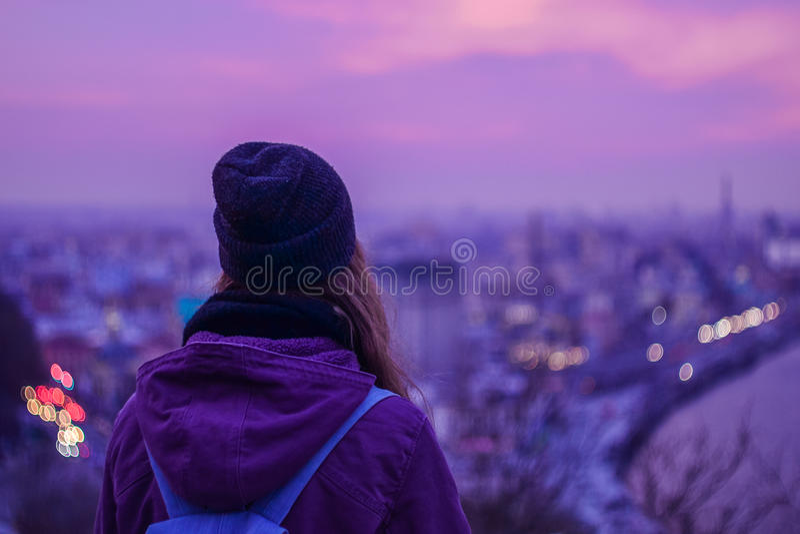 Viajante da menina do moderno que olha a arquitetura da cidade da noite do inverno, o céu violeta roxo e as luzes da cidade foto de stock royalty free