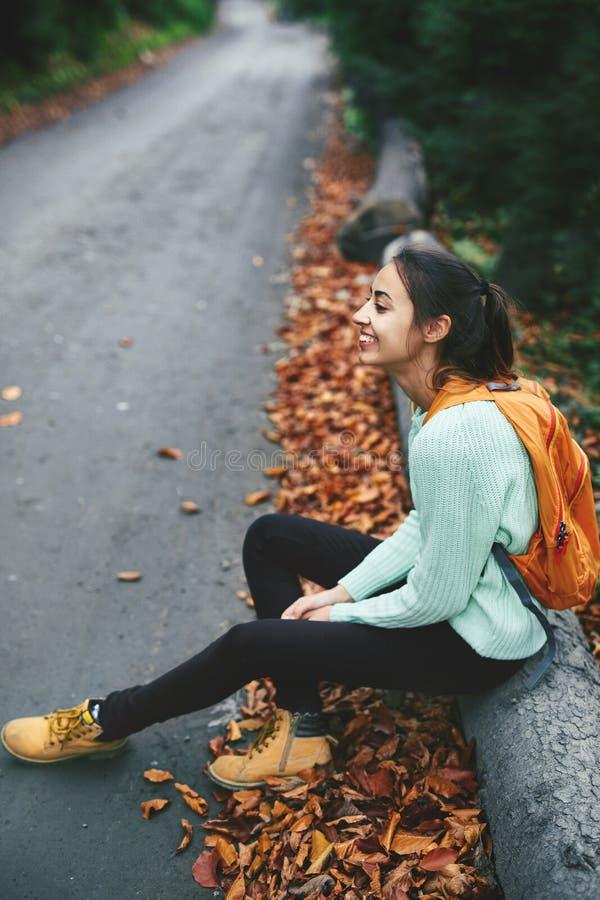Viajante da menina em botas amarelas e na camiseta da hortelã, sentando-se no log grande perto da estrada na floresta do outono fotografia de stock royalty free