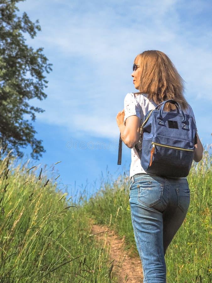 Viajante da menina que caminha com a trouxa em prados alpinos Férias de verão da aventura do conceito do estilo de vida do curso  fotografia de stock