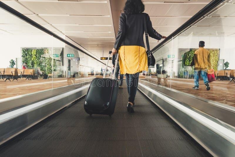 Viajante da moça que anda com a mala de viagem levando da posse no a fotografia de stock