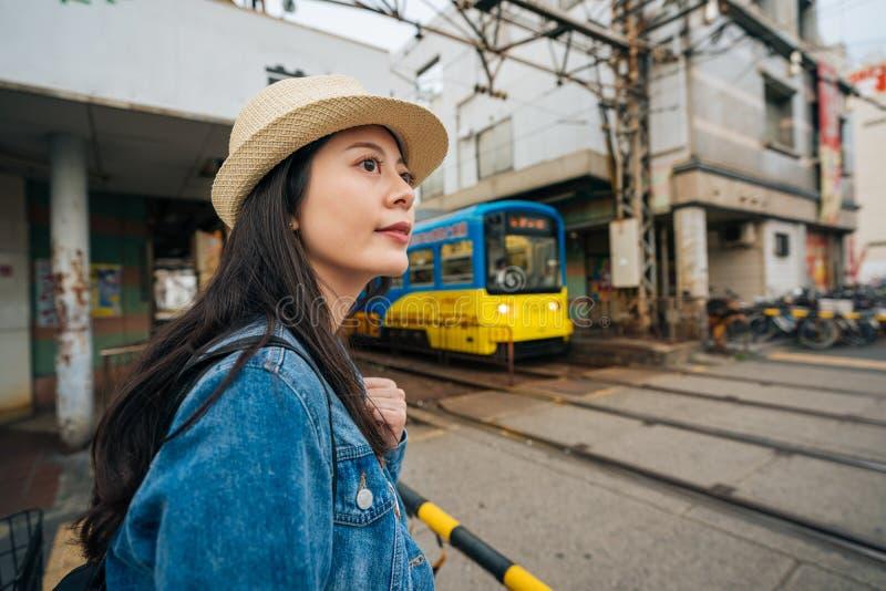Viajante da moça que espera a passagem do trem e que olha o sinal pronto para cruzar a estrada de ferro turista elegante da senho fotografia de stock royalty free