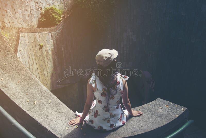 Viajante da moça que senta-se em escadas do círculo de um stairca espiral fotografia de stock