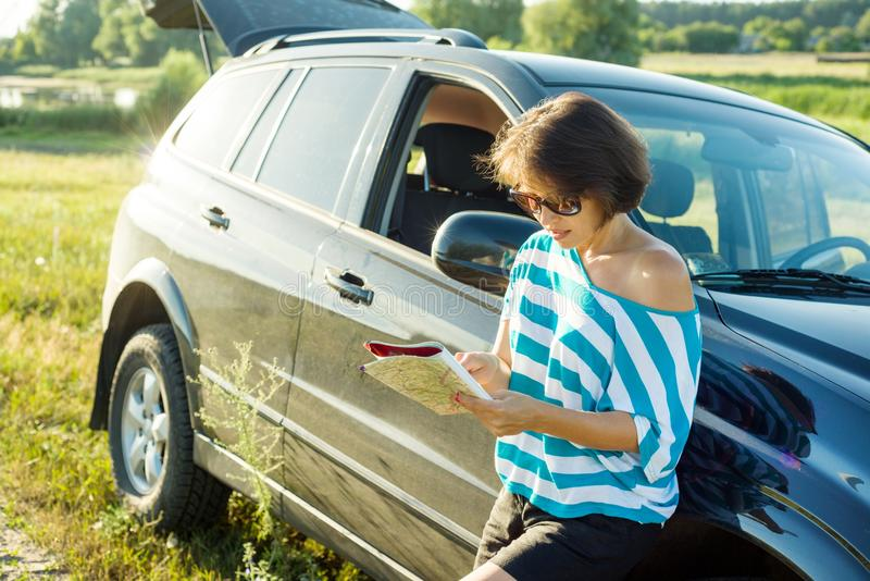 Viajante da mulher adulta que olha no mapa do turista que está perto do carro na estrada rural imagens de stock