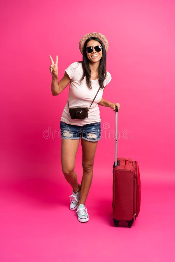 Viajante da mulher com a mala de viagem no fundo da cor imagem de stock royalty free