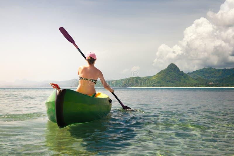 Viajante da mulher que explora a praia tropical calma pela canoa imagem de stock