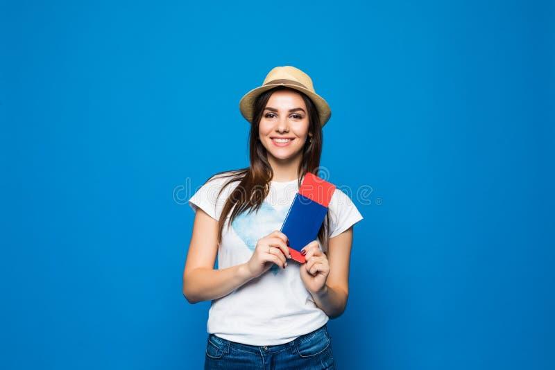 Viajante da mulher que guarda o passaporte com bilhete Retrato da menina feliz de sorriso pronta para o curso no fundo azul foto de stock