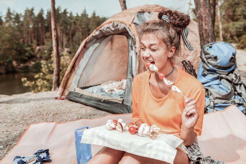 Viajante de cabelo escuro encaracolado que come cogumelos com os tomates após a noite na barraca fotografia de stock royalty free